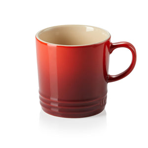 A red ombre mug with a handle and a beige in interior
