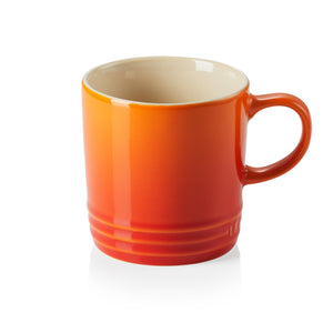 A red and orange ombre mug with a handle and beige interior