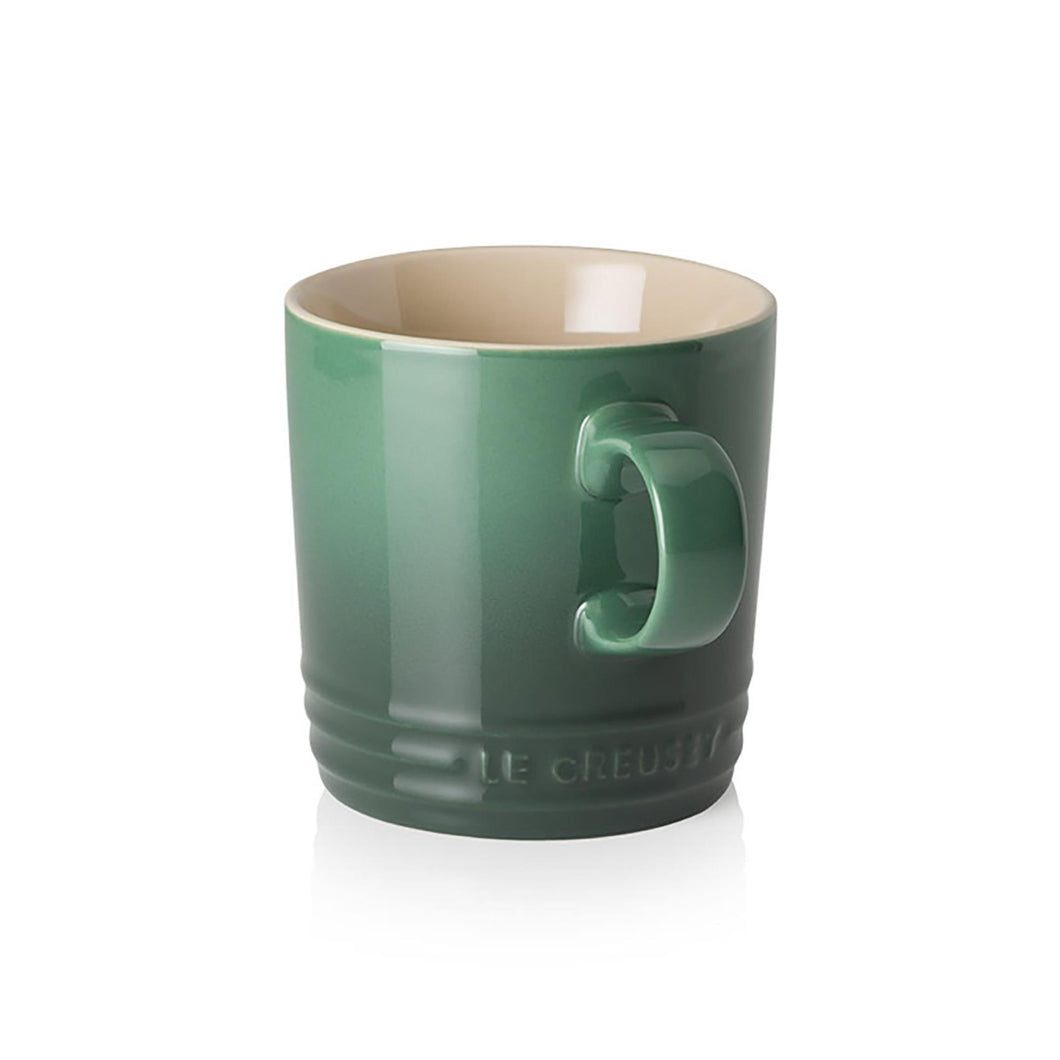 A green ombre mug with a handle and a beige interior