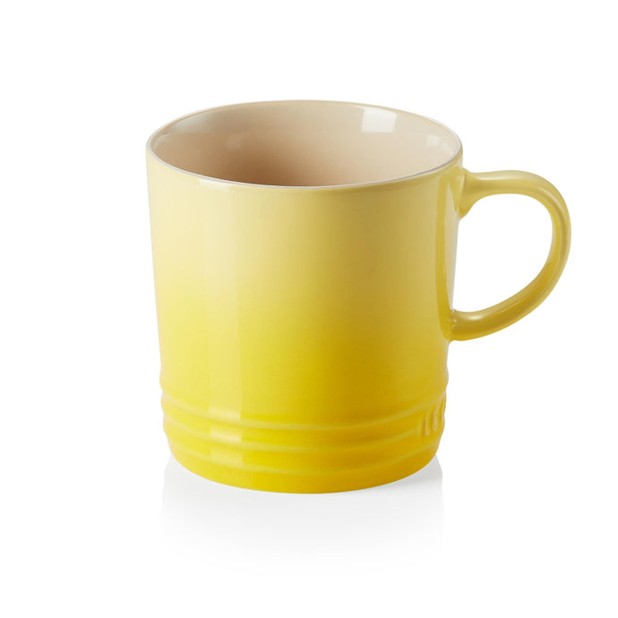 A yellow ombre mug with a handle and beiege imterior