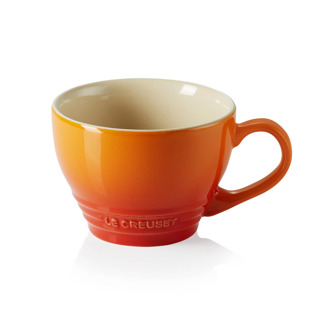 A red and orange ombre stoneware mug with a beige interior and embossed le creuset logo