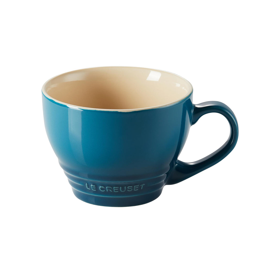 A blue ombre stoneware mug with a beige interior and embossed le creuset logo
