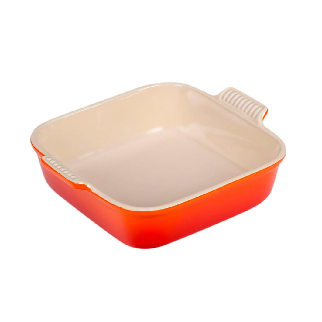 A square stoneware dish with a red and orange ombre exterior and a beige interior