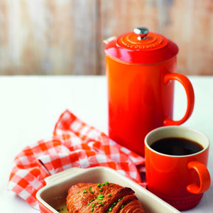 The cafetiere shown with a mug of coffee in a matching mug and a criossant in a matching dish