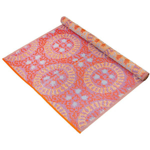 orange patterned outdoor rug rolled up