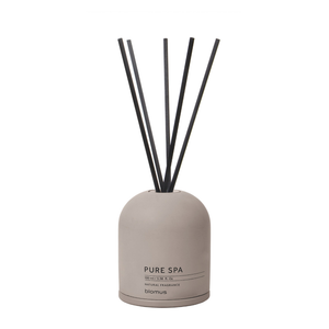 A Royal Leather scented reed diffuser with a concrete base