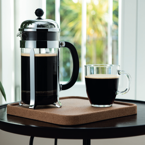 A French Press filled with coffee which has a glass beaker, chrome hardware and a plastic handle sitting on a coffee table next to a filled glass coffee cup