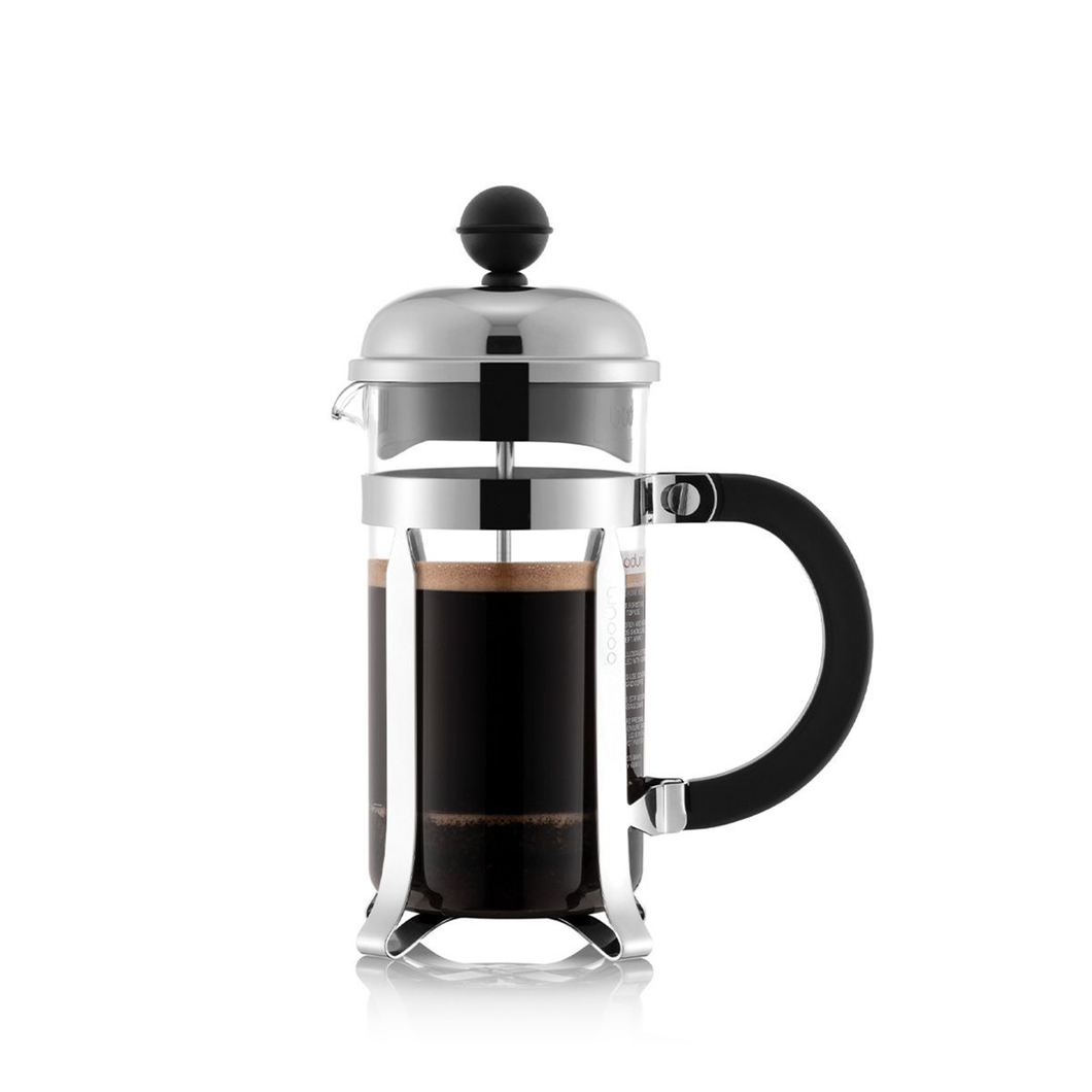 A small french press with a glass beaker, chrome hardware and a plastic handle filled with freshly brewed coffee