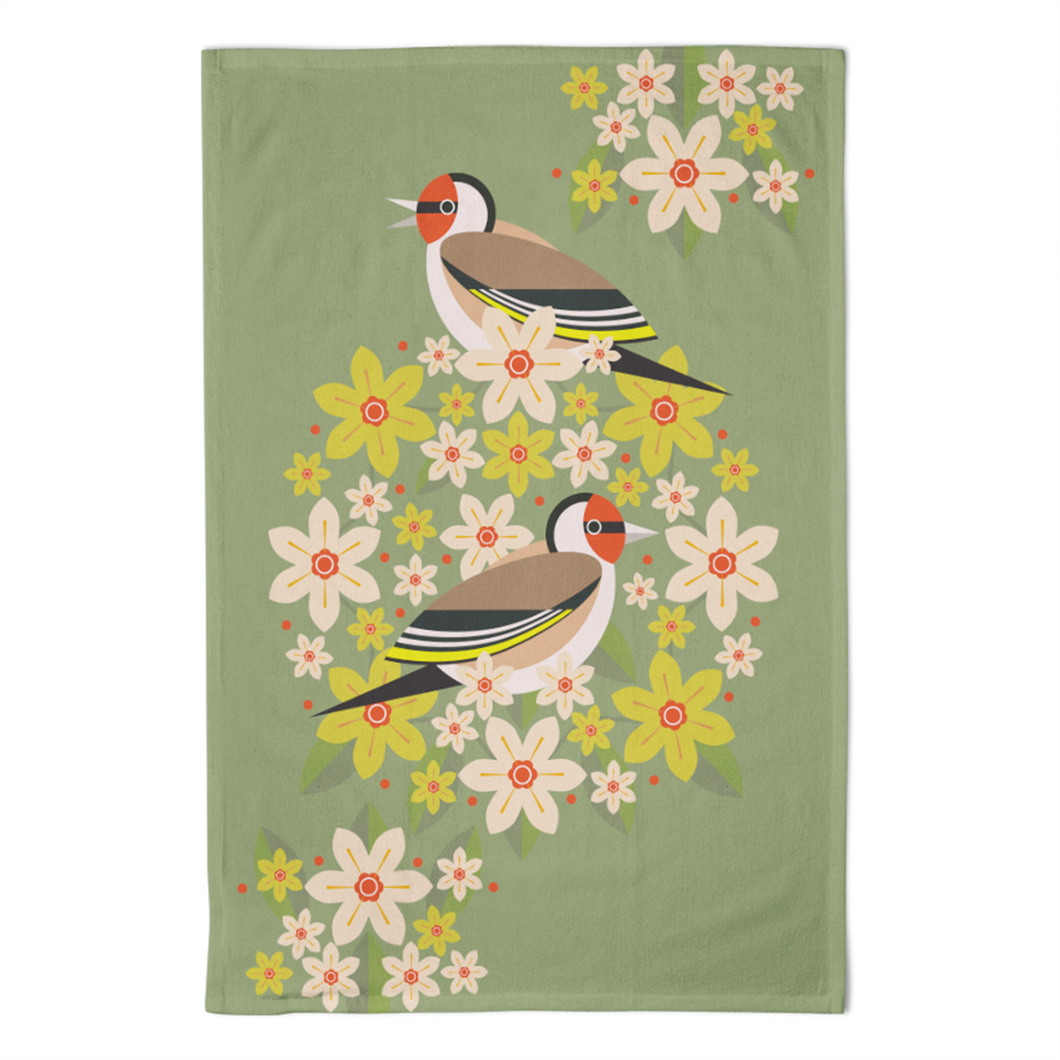 A green tea towel with a floral design and two large goldfinches