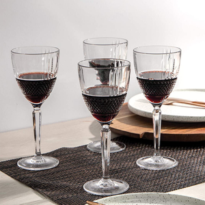 Four crystaline glasses with embossed diamond-cut bands filled with red wine arranged on on a dining table