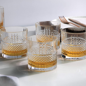 Four crystaline tumblers with and embossed diamond cut band displayed on a dining tabled filled with whisky