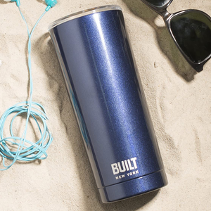 the travel mug on a sandy beach