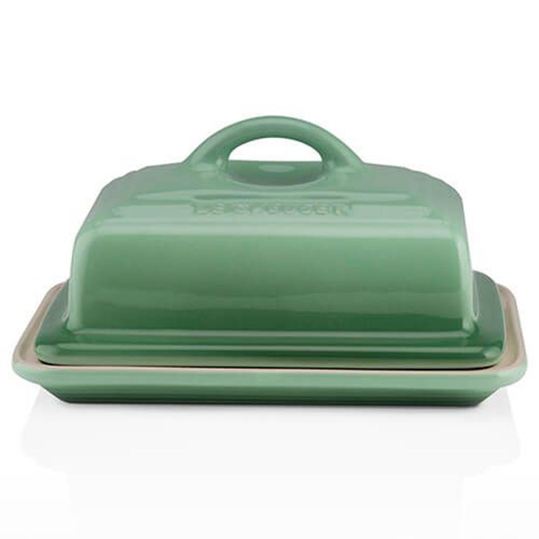 a green stoneware butter dish with a lid