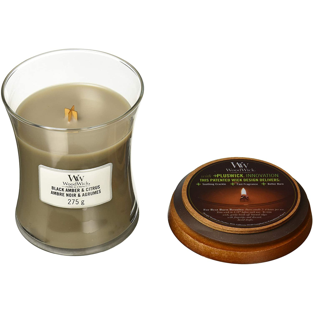 A medium candle in a glass jar with it's lid removed to display the wooden wick