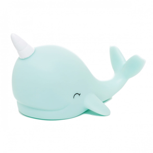 A small blue  narwhal night light with a white horn
