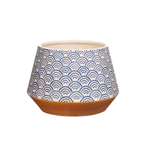 a geometric plant pot with a blue scalloped arch design and an orange band at the bottom