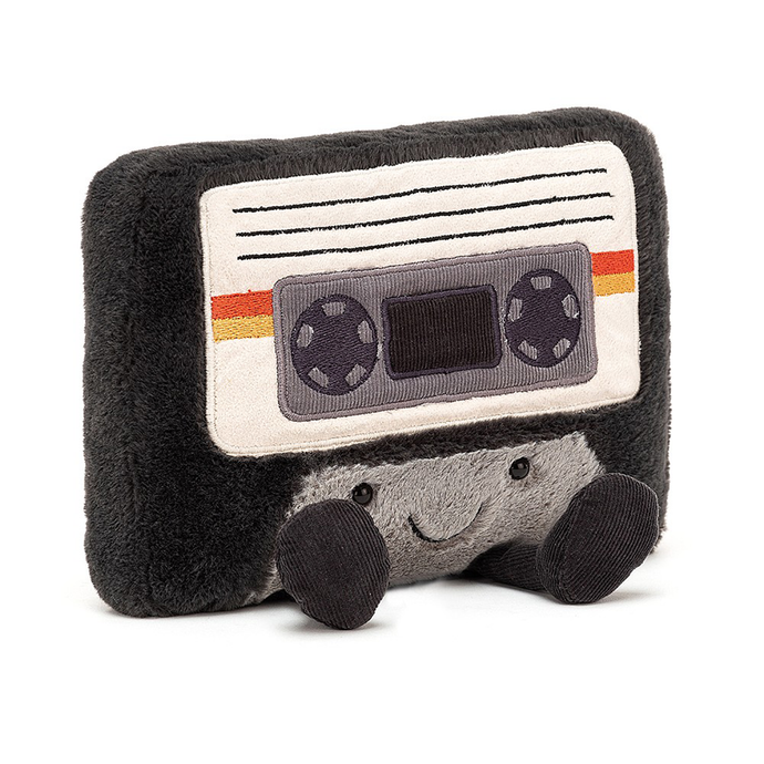 a grey cassette tape shaped plushie with a smiley face and legs