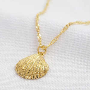 a gold clain with a textured clam shell pendant