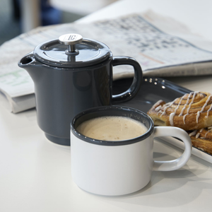 The french press with the mug filled with coffree served with pastries and a newpaper