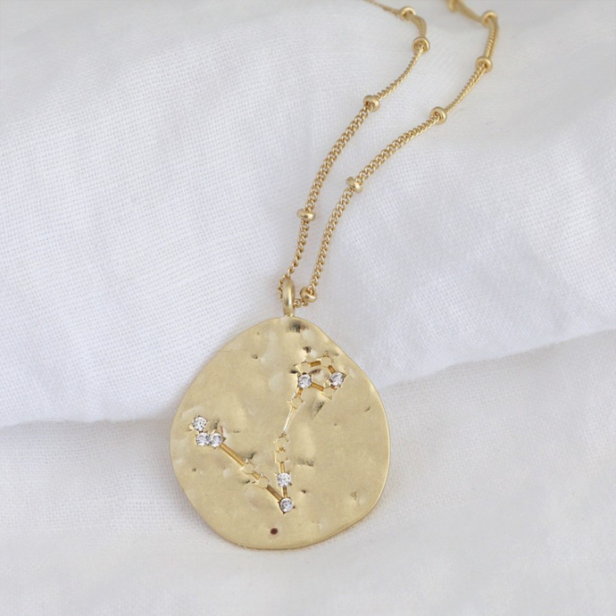 a gold necklace with a hammered pendant featuring a constellation design