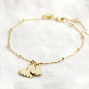 a chain braclet with small beads and two heart charms