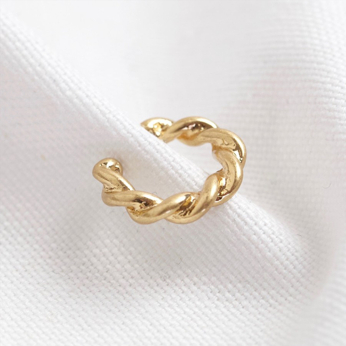 a gold ear cuff with a twisted design
