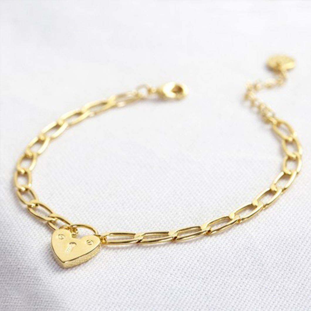 a gold chain bracelet with a heart lock charm