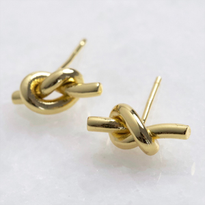 A pair of gold stud earrings with a knot shape