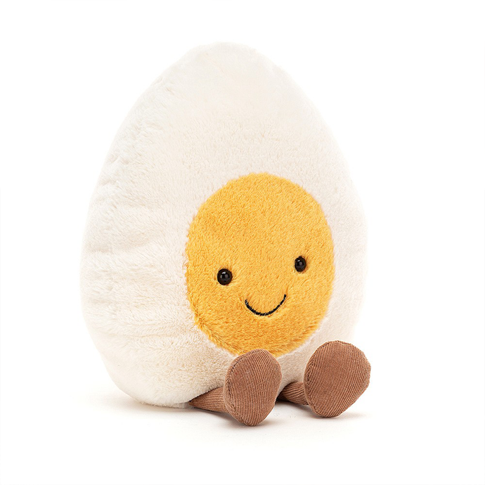 a soft toy shaped like a halved boiled egg with a smiley face and corduroy legs