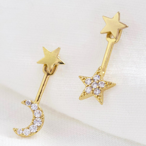 A pair of star stud earrings with a bejewelled dangly moon and star