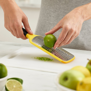 The multi-grate paddle grater zesting a lime