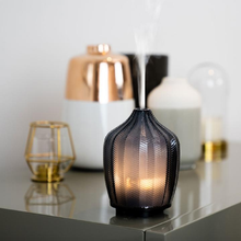 Load image into Gallery viewer, the aroma diffuser on a cabinet, letting out a mist
