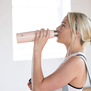 a woman drinking out of the water bottle