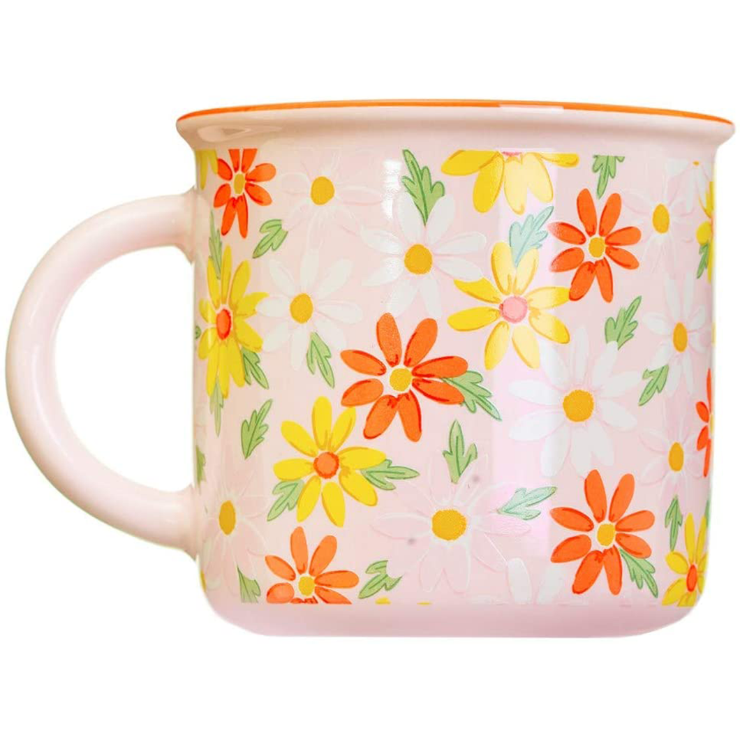 a pink mug with a white orange and yellow daisy pattern