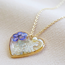 Load image into Gallery viewer, A heart shaped pendant with pressed flowers in resin and a pearl