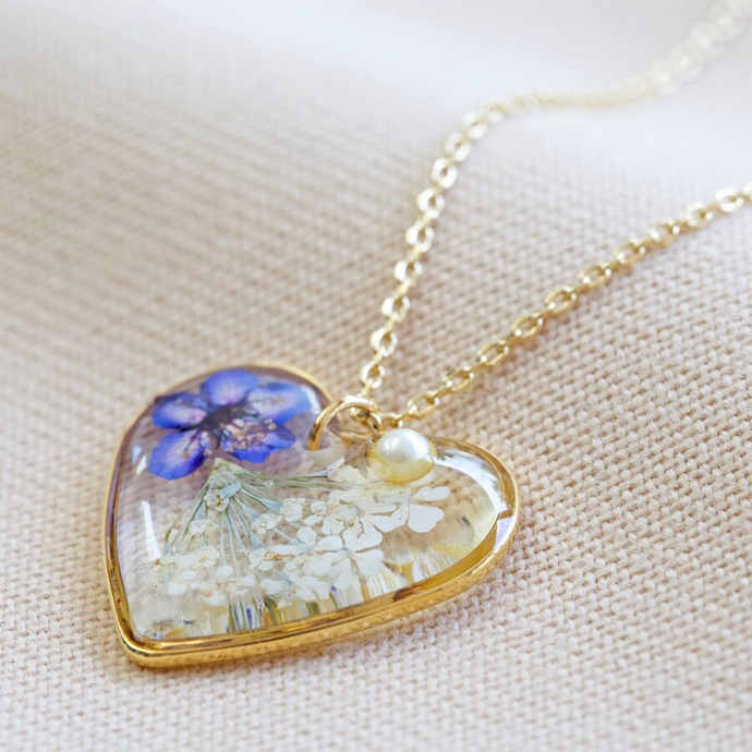 A heart shaped pendant with pressed flowers in resin and a pearl