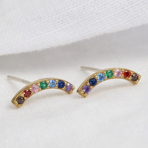 a pair of stud earrings comprising of a gold curve with rainbow coloured gems accross it