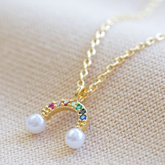 a tiny rainbow pendant with multi coloured jewels and pearl clouds