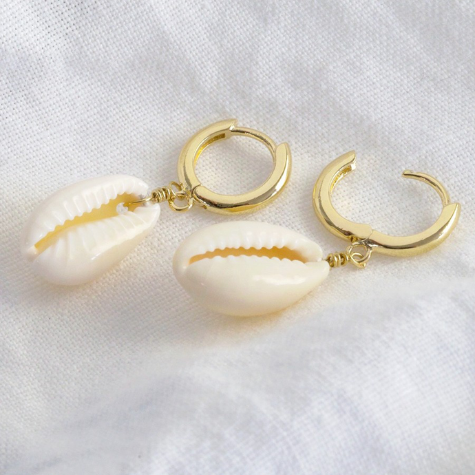 a pair of gold huggie style earrings with a rea cowrie sheel charm