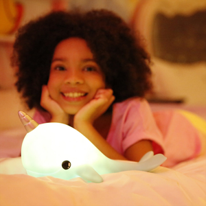 a little girl posing with her sky sky narwhal night light