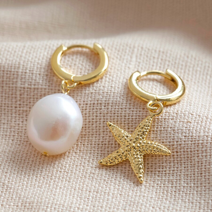 a pair of gold huggie style earrings - one with a starfish charm, the other with a pearl charm