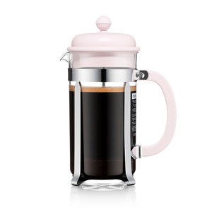 A french press with a glass tumbler and stainless steel and pink plastic hardware