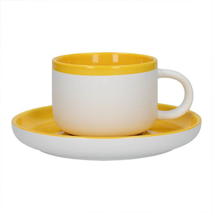 a white tea cup with a yellow rim and interior sat atop a saucer with a yellow top and white bottom