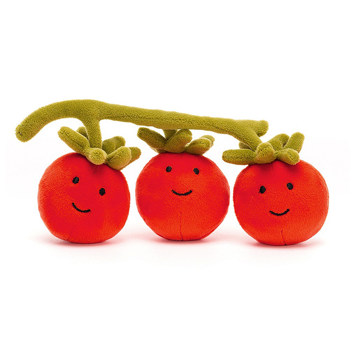 Three smiling red tomatoes on a green vine