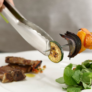 the tongs being used to take a peice of courgette of a skewer