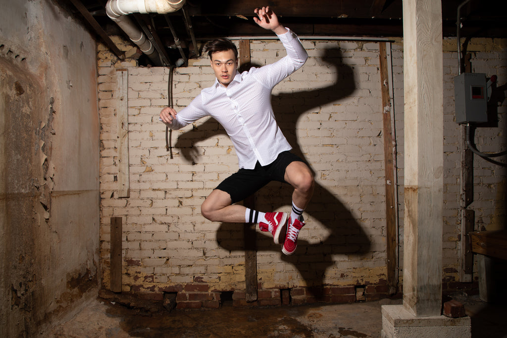 Young Man in white dress shirt leaping in excitement. ALL COTTON