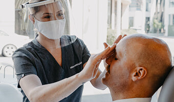 A consultant wearing a mask with a patient