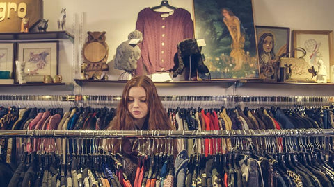 A woman browses racks of clothing inside thrift stores, second hand stores and discount stores, which can be a great place for drag queens to shop for clothing