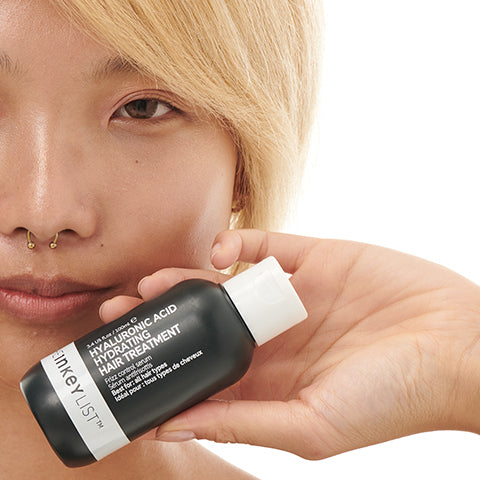 Model with Hyaluronic Acid Hydrating Hair Treatment bottle