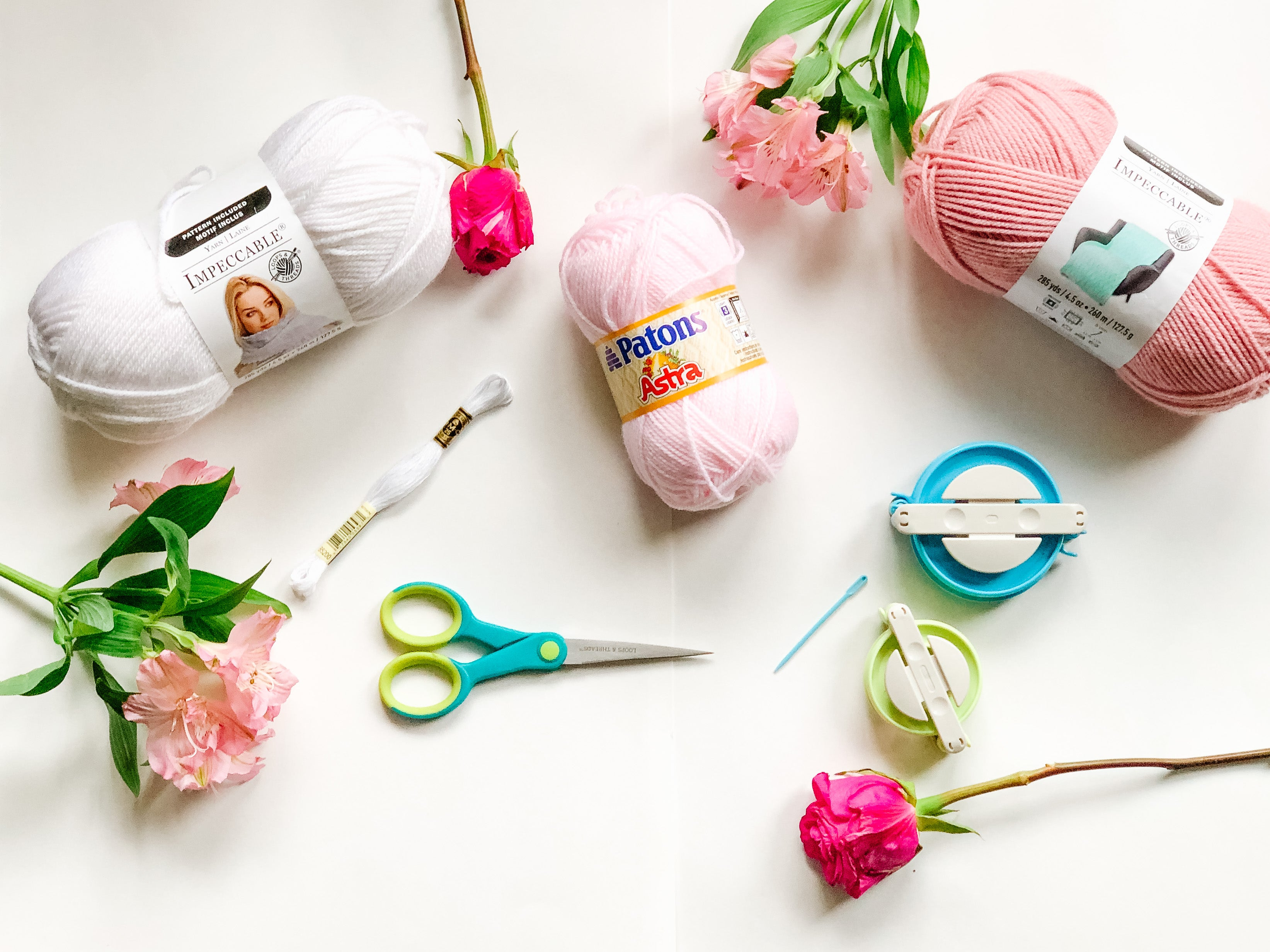 yarn for diy pom pom garland on white surface with flowers and scissors